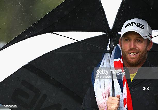 Adam Bland of Australia waits under an umbrella during round three of the Australian Masters at The Victoria Golf Club on November 13 2010 in...