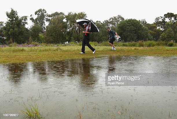 Adam Bland of Australia walks up the flooded fairway during round three of the Australian Masters at The Victoria Golf Club on November 13 2010 in...