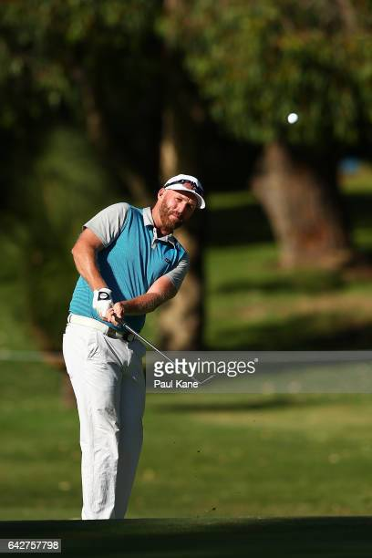 Adam Bland of Australia watches his chip shot on the 4th hole during match four of the match play during round four of the ISPS HANDA World Super 6...