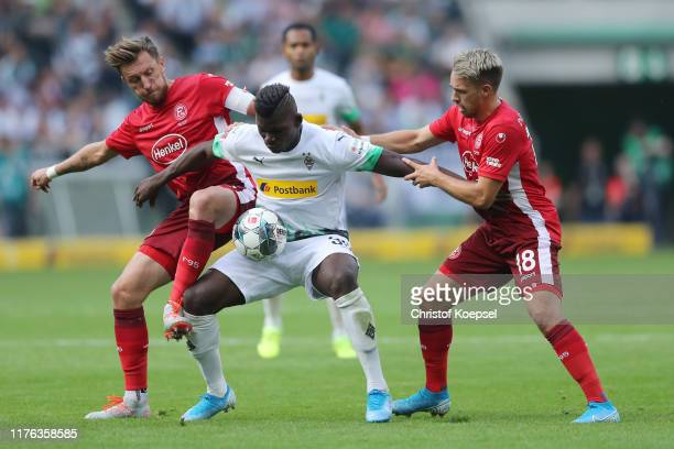 Adam Bodzek of Duesseldorf and Thomas Pledl of Duesseldorf challenge Breel Embolo of Moenchengladbach during the Bundesliga match between Borussia...