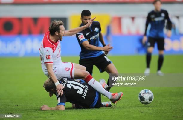 Adam Bodzek of Duesseldorf falls onto Ben Zolinski of Paderborn during the Bundesliga match between SC Paderborn 07 and Fortuna Duesseldorf at...