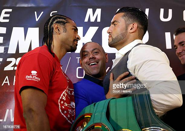 Adam Booth steps between David Haye and Manuel Charr during a press conference to announce their upcoming Heavyweight bout at Manchester Arena on May...