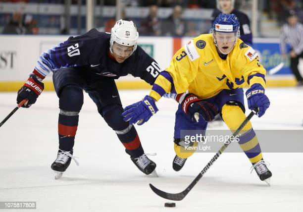 Adam Boqvist of Sweden skates with the puck while being chased by K'Andre Miller of the United States at the IIHF World Junior Championships at the...