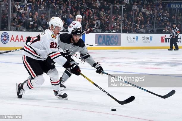 Adam Boqvist of the Chicago Blackhawks and Michael Amadio of the Los Angeles Kings battle for the puck during the first period against the Chicago...