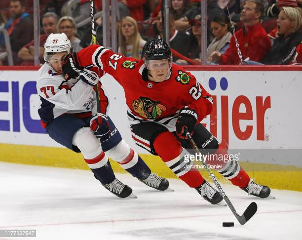 Adam Boqvist of the Chicago Blackhawks controls the puck in front of TJ Oshie of the Washington Capitals during a preseason game at the United Center...