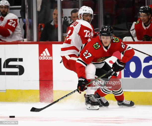 Adam Boqvist of the Chicago Blackhawks is pressured by Andreas Athanasiou of the Detroit Red Wings during a preseason game at the United Center on...