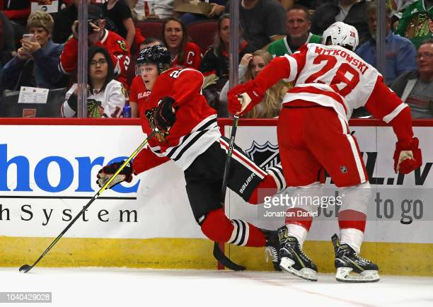 Adam Boqvist of the Chicago Blackhawks is tripped up by Luke Witkowski of the Detroit Red Wings during a preseason game at the United Center on...