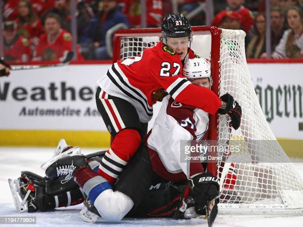 Adam Boqvist of the Chicago Blackhawks shoves JT Compher of the Colorado Avalanche into the goal and on top of Corey Crawford at the United Center on...