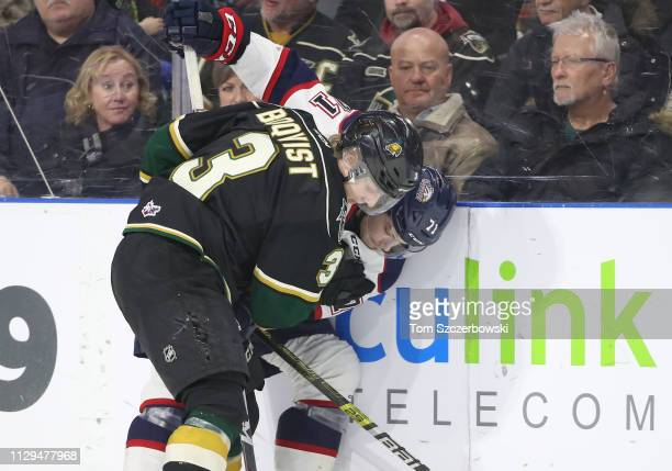 Adam Boqvist of the London Knights is tied up with Nicholas Porco of the Saginaw Spirit as they battle for the puck along the side boards in the...
