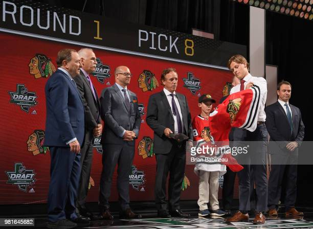 Adam Boqvist puts on a Chicago Blackhawks jersey onstage after being selected eighth overall by the Chicago Blackhawks during the first round of the...