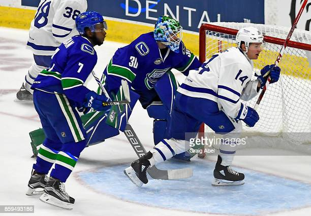 Adam Brooks of the Toronto Marlies battles for crease space with Jordan Subban and Thatcher Demko of the Utica Comets with during AHL game action on...