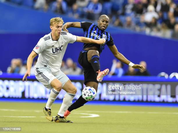 Adam Buksa of New England Revolution and Rod Fanni of the Montreal Impact chase the ball in the second half during the MLS game at Olympic Stadium on...
