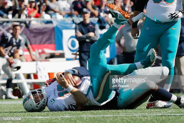 Adam Butler of the New England Patriots sacks Ryan Tannehill of the Miami Dolphins during the second half at Gillette Stadium on September 30 2018 in...
