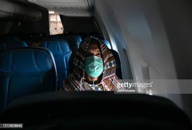 Adam Carver wears a mask to protect against coronavirus while on a nearly empty Delta flight from Seattle-Tacoma International Airport o JFK on March...