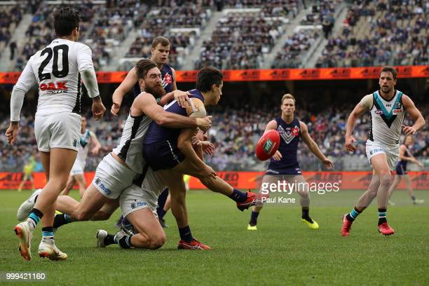 Adam Cerra of the Dockers gets his kicks away while being tackled by Charlie Dixon of the Power during the round 17 AFL match between the Fremantle...