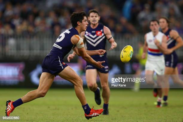Adam Cerra of the Dockers handballs during the round five AFL match between the Fremantle Dockers and the Western Bulldogs at Optus Stadium on April...