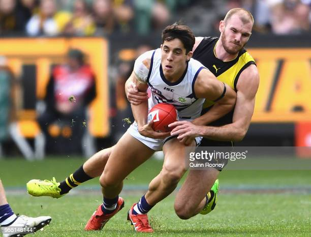 Adam Cerra of the Dockers is tackled by Kamdyn McIntosh of the Tigers during the round seven AFL match between the Richmond Tigers and the Fremantle...