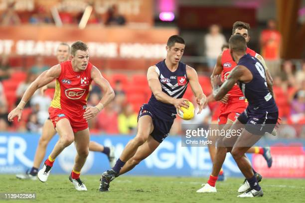 Adam Cerra of the Dockers kicks during the round two AFL match between the Gold Coast Suns and the Fremantle Dockers at Metricon Stadium on March 31...