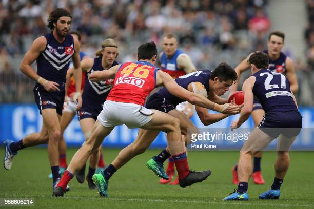 Adam Cerra of the Dockers looks to break from a tackle by Oscar McInerney of Lions during the round 15 AFL match between the Fremantle Dockers and...
