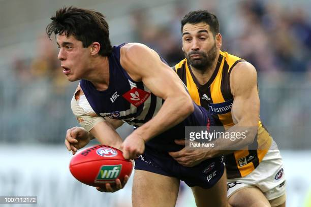 Adam Cerra of the Dockers looks tohandball against Paul Puopolo of the Hawks during the round 19 AFL match between the Fremantle Dockers and the...