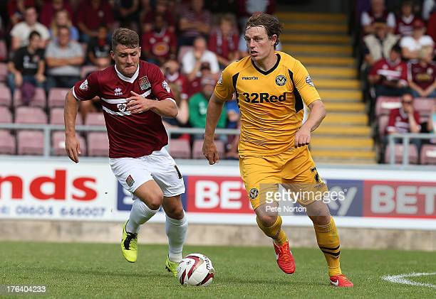 Adam Chapman of Newport County AFC looks to play the ball watched by Gary Deegan of Northampton Tow during the Sky Bet League Two match between...