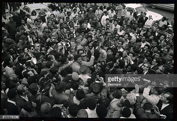 Adam Clayton Powell, self-exiled Harlem Democrat, , waves as he is surrounded by a cheering crowd as he began his tour of South Central and the Watts...