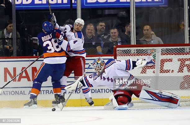 Adam Clendening and Antti Raanta of the New York Rangers defend against Eric Boulton of the New York Islanders during the first period at the...