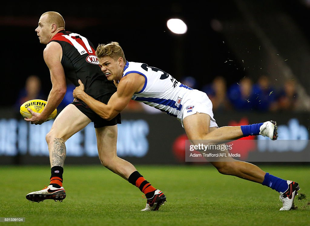 Adam Cooney of the Bombers is tackled by Mason Wood of the Kangaroos during the 2016 AFL Round 08 match between the Essendon Bombers and the North Melbourne Kangaroos at Etihad Stadium, Melbourne on May 14, 2016 in Melbourne, Australia.