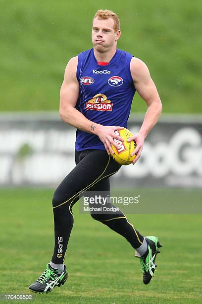 Adam Cooney runs with the ball during a Western Bulldogs AFL training session at Whitten Oval on June 13 2013 in Melbourne Australia