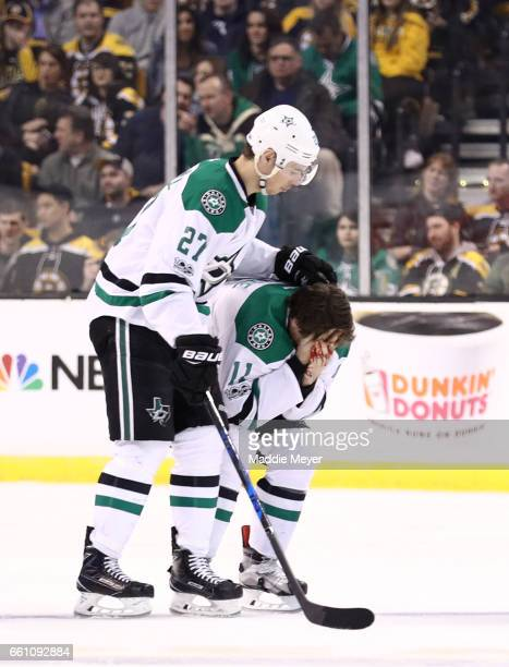 Adam Cracknell of the Dallas Stars assists his injured teammate Curtis McKenzie during the third period against the Boston Bruins at TD Garden on...
