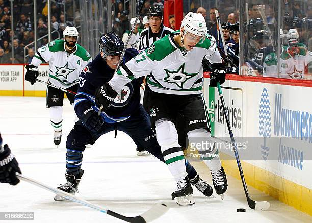 Adam Cracknell of the Dallas Stars holds off Brandon Tanev of the Winnipeg Jets as he plays the puck down the ice during third period action at the...