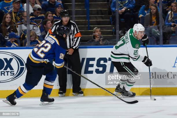 Adam Cracknell of the Dallas Stars skates with the puck as Chris Thorburn of the St Louis Blues pressures at Scottrade Center on October 7 2017 in St...
