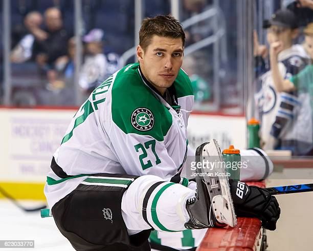 Adam Cracknell of the Dallas Stars stretches at the bench during the pregame warm up prior to NHL action against the Winnipeg Jets at the MTS Centre...