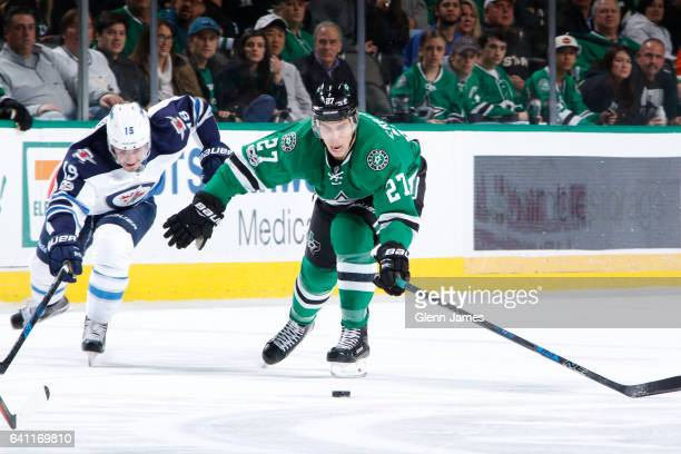 Adam Cracknell of the Dallas Stars tries to keep the puck away against Nic Petan of the Winnipeg Jets at the American Airlines Center on February 2...