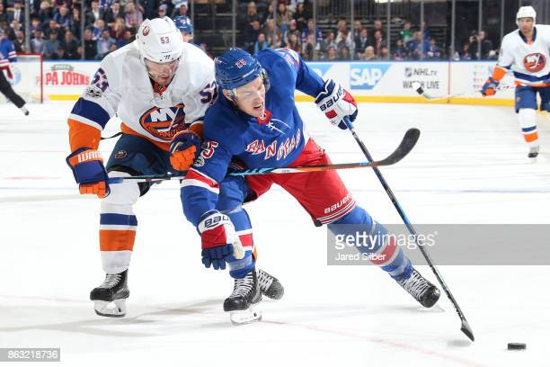 Adam Cracknell of the New York Rangers skates with the puck against Casey Cizikas of the New York Islanders at Madison Square Garden on October 19...