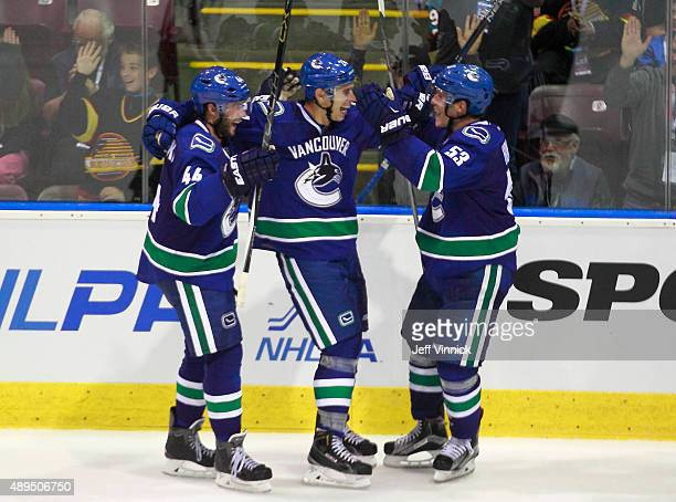 Adam Cracknell of the Vancouver Canucks celebrates his overtime goal with teammates Matt Bartkowski and Bo Horvat during their game against the San...