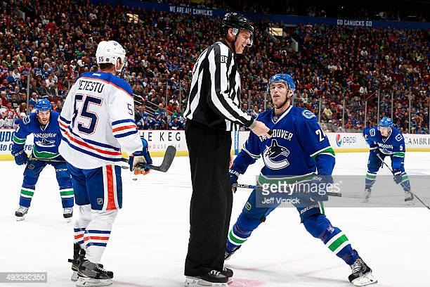 Adam Cracknell of the Vancouver Canucks looks up at linesman Mike Cvik as he prepares to take a faceoff against Mark Letestu of the Edmonton Oilers...