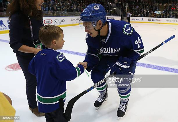 Adam Cracknell of the Vancouver Canucks shakes hands with a young fan after the Canucks played the San Jose Sharks during Day 3 of NHL Kraft...