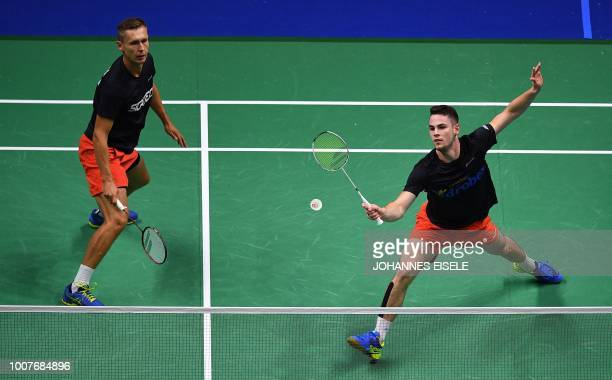 Adam Cwalina of Poland watches as teammate Milosz Bochat hits a shot against Han Chengkai and Zhou Haodong of China in their men's doubles match...