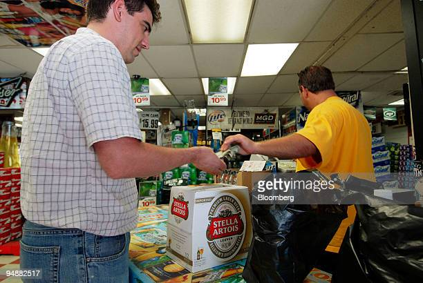 Adam Davison pays for his purchases including a 12pack of InBev's Stella Artois beer at Beverage World in the Brooklyn borough of New York US on...