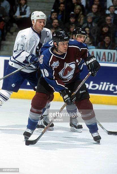 Adam Deadmarsh and Joe Sakic of the Colorado Avalanche battle for position with Mats Sundin of the Toronto Maple Leafs on February 17, 2001 at the...