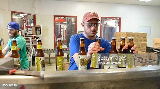 Adam DeFelice catches bottles of the Hookiebobb IPA for packaging as Crazy Mountain Brewery bottles it's beer on Tuesday December 08 2015 at it's...