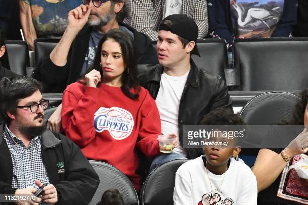 Adam DeVine and Chloe Bridges attend a basketball game between the Los Angeles Clippers and the Dallas Mavericks at Staples Center on February 25...