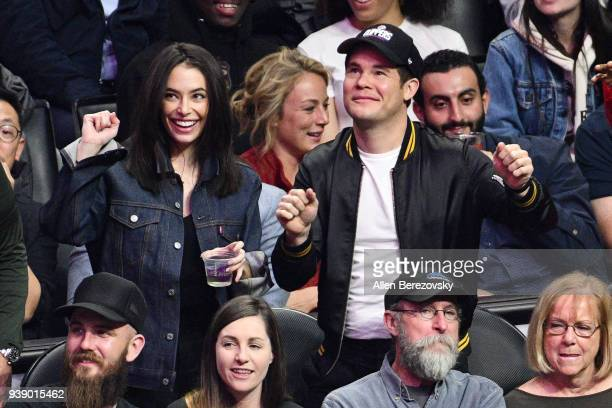 Adam Devine and Chloe Bridges attend a basketball game between the Los Angeles Clippers and the Milwaukee Bucks at Staples Center on March 27 2018 in...