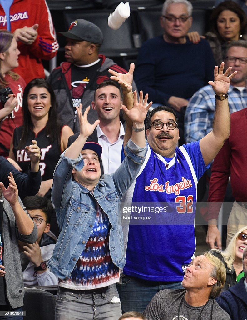 Adam DeVine (L) and Erik Griffin attempt to grab a shirt at a basketball game between the Miami Heat and the Los Angeles Clippers at Staples Center on January 13, 2016 in Los Angeles, California.