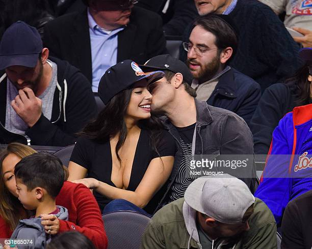 Adam DeVine kisses Chloe Bridges at a basketball game between the Oklahoma City Thunder and the Los Angeles Clippers at Staples Center on January 16...