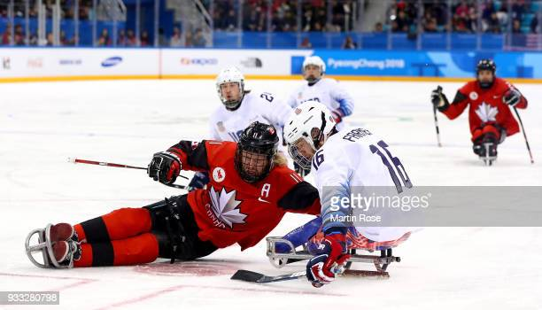 Adam Dixon of Canada battles for the puck with Declan Farmer of United States in the Ice Hockey gold medal game between Canada and United States...