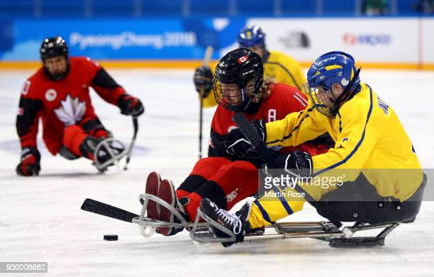 Adam Dixon of Canada battles for the puck with Peter Ojala of Sweden in the Ice Hockey Preliminary Round Group A game between Canada and Sweden...