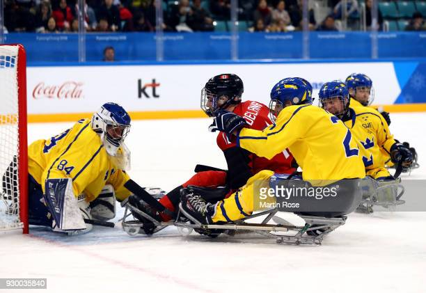 Adam Dixon of Canada fails to score over Andreas Nejman goaltender of Sweden in the Ice Hockey Preliminary Round Group A game between Canada and...