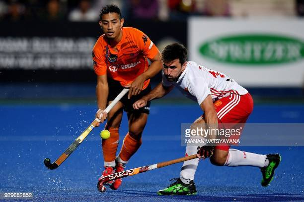Adam Dixon of England vies for the ball with Malaysia's Firhan Ashari during their men's field hockey match of the 2018 Sultan Azlan Shah tournament...